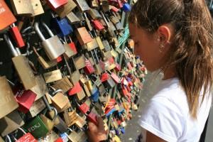 los enamorados sellan su amor colgando candados y arrojando la llave al agua